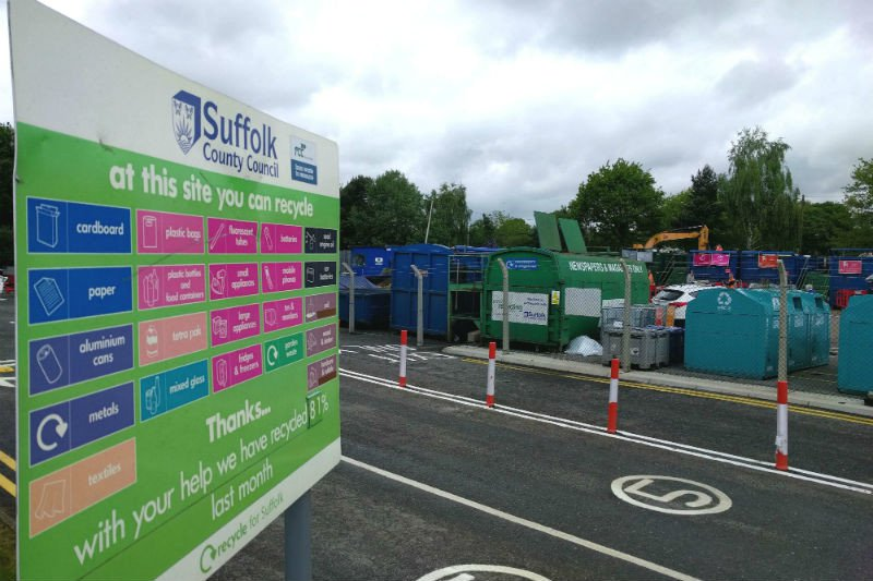 Recycling centre entrance with board and bins
